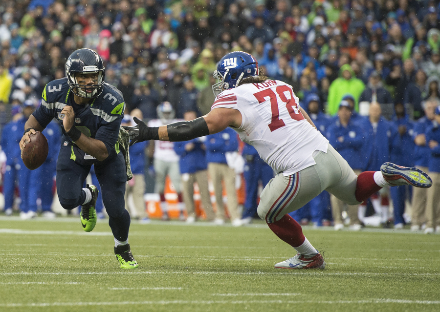 Seahawks quarterback Russell Wilson scrambles to avoid the Giants defensive lineman Markus Kuhn on Sunday, Nov. 9, 2014 at CenturyLink Field.